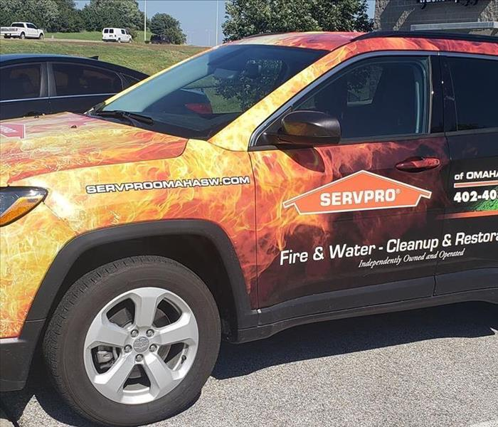 Wrapped Jeep with orange Fire and Green Water with SERVPRO logo and SERVPRO of Omaha Southwest's contact info