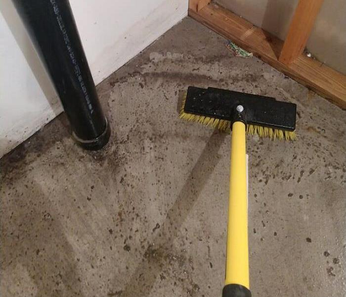 dirty floor with black and yellow push broom cleaning up the mess